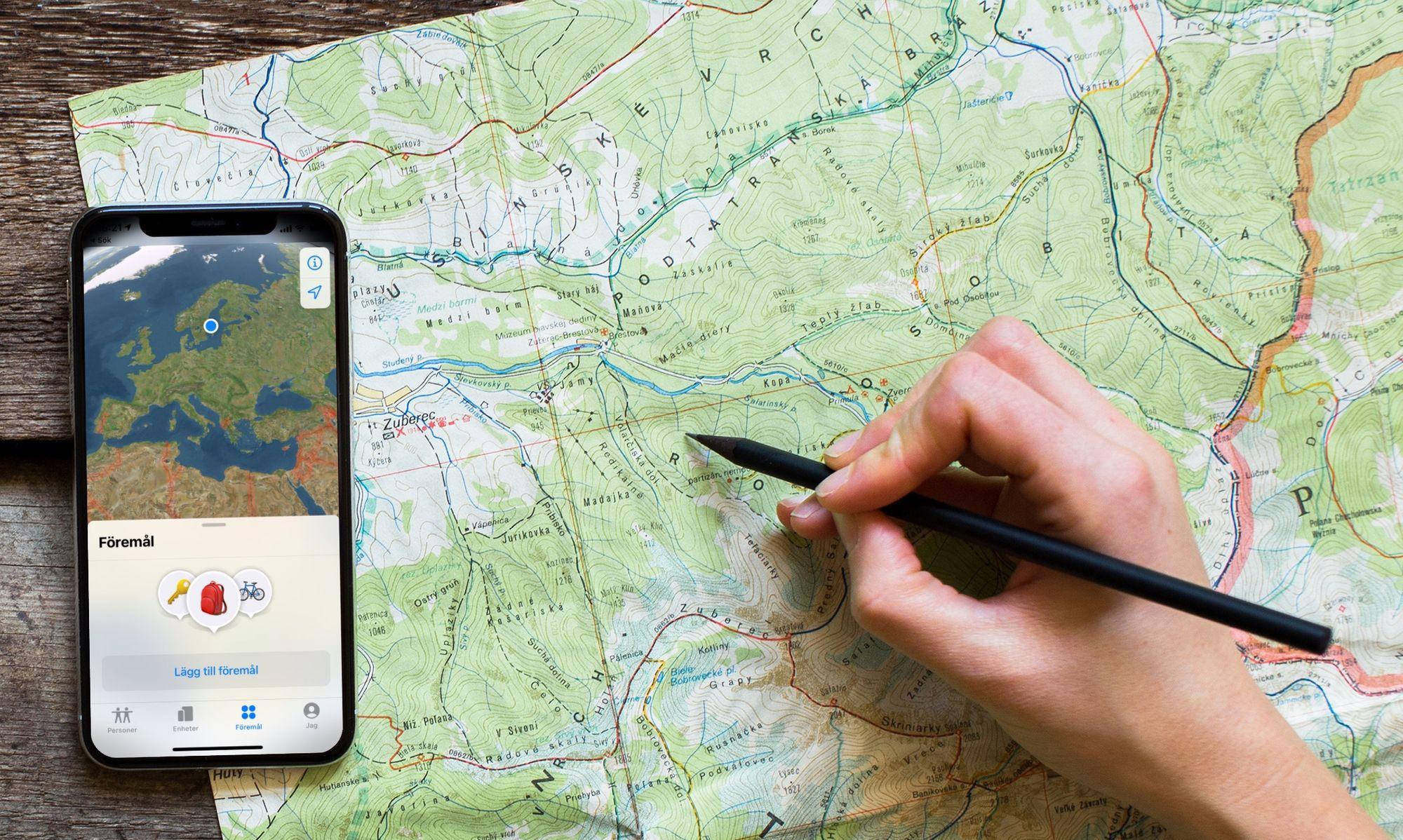 """Bild på iPhone med appen Hitta och menyvalen """"Föremål"""" markerat tillsammans med en karta. Telefonen ligger på ett bord med en fysisk karta och en hand som markerar en position på en karta med en penna."""